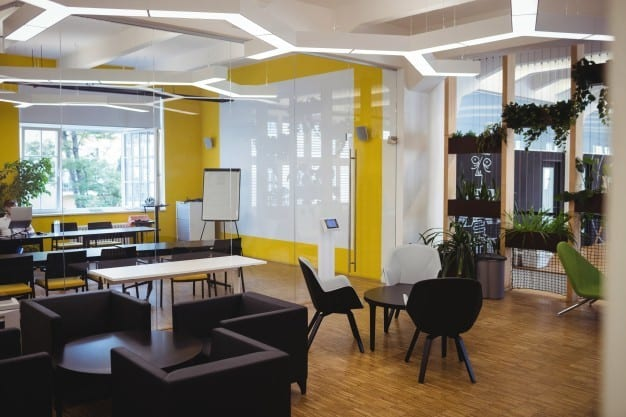 A modern open office plan with black furniture, yellow walls, and wooden flooring.