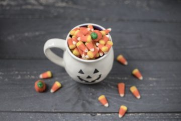 Halloween mug full of candy corn on a wooden floor
