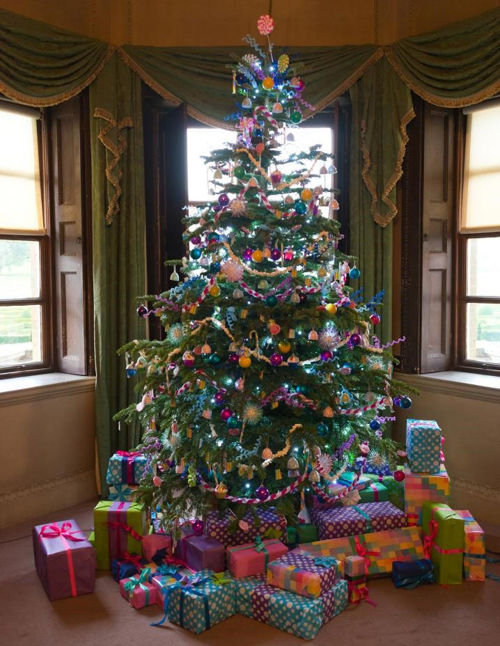Decorated Christmas tree and gifts on carpet flooring.