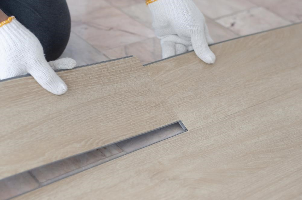 A flooring specialist installing vinyl tiles that mimic the look of hardwood.
